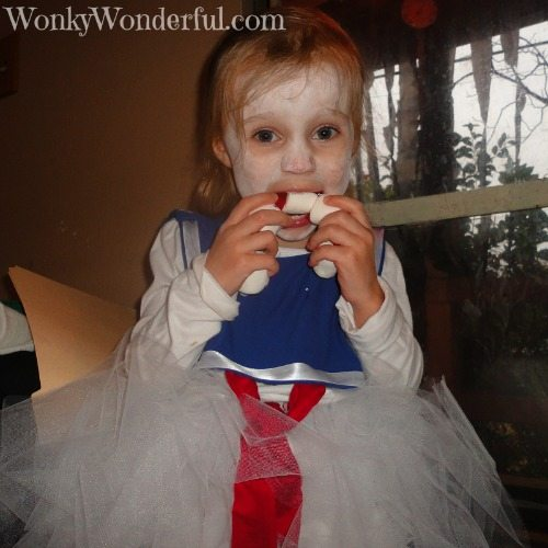 little girl eating marshmallow necklace