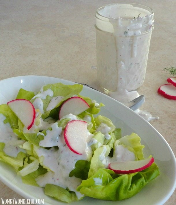 ranch dressing dripping over the side of clear glass jar next to plate with lettuce, sliced radishes and dressing