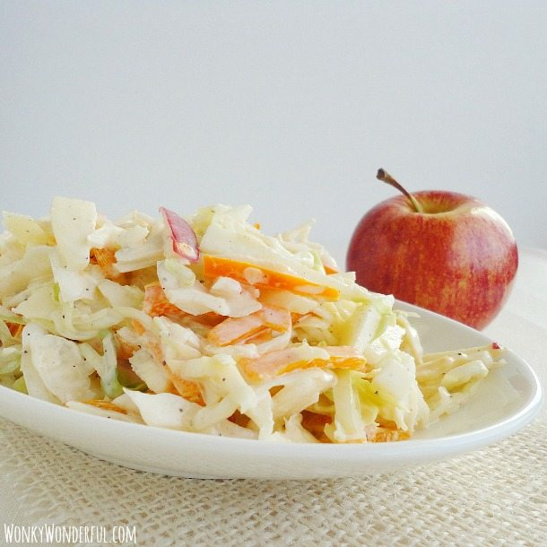 Apple Cabbage Coleslaw in white serving dish with apple on the side