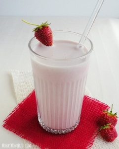 pink beverage in clear glass with strawberry