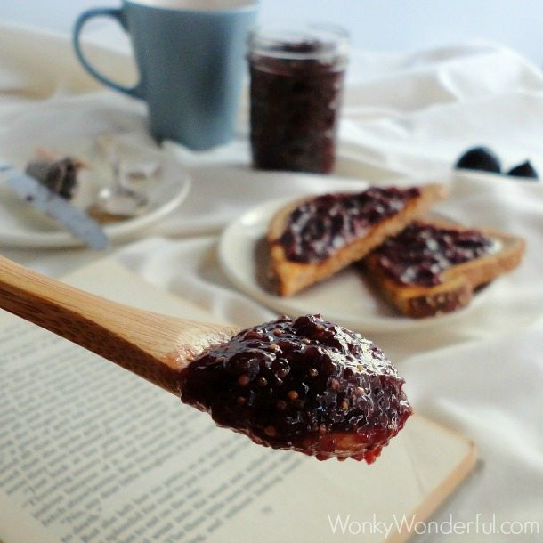 wooden spoon topped with fig jam, toast and tea in the background