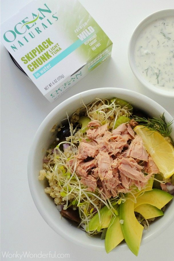 tuna, avocados, sprouts and quinoa in white bowl next to package of canned tuna