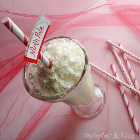 white milkshake in clear milkshake glass topped with whipped cream and a red and white striped straw with north pole sign attached