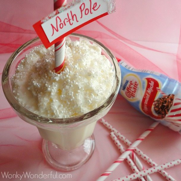 white milkshake in clear milkshake glass topped with whipped cream and a red and white striped straw with north pole sign attached - coffee mate creamer bottle on the side