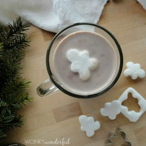 overhead view of cocoa in glass mug with gingerbread shaped marshmallow on top