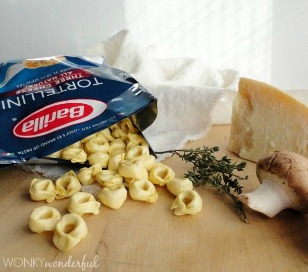package of dried tortellini, thyme, mushroom and parmesan chunk on wood cutting board