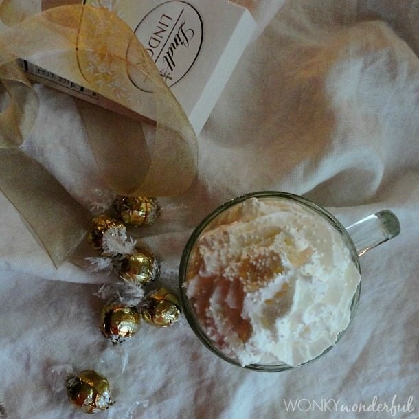 overhead view of gold wrapped truffles, mug of hot chocolate and Lindt package