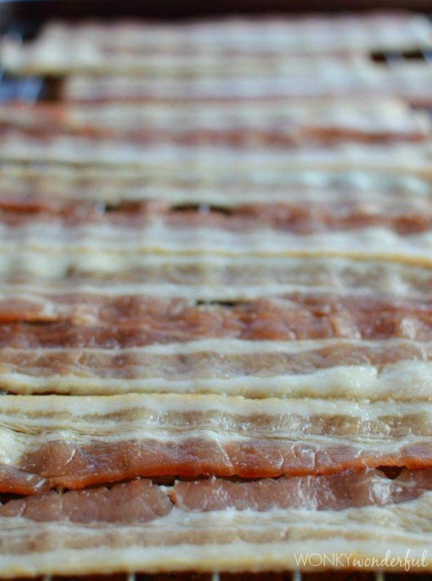 raw bacon strips on wire rack