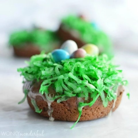 brown donut topped with green coconut and egg shaped candy
