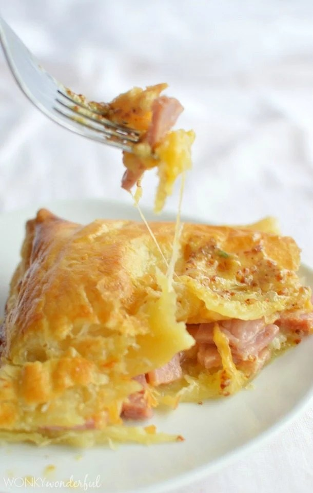 golden baked pastry filled with ham and cheese with fork getting bite