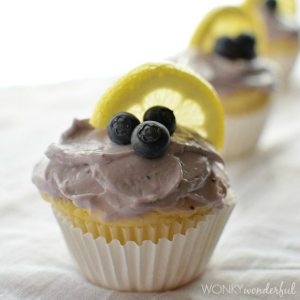 yellow muffin in white wrapper topped with frosting blueberries and lemon