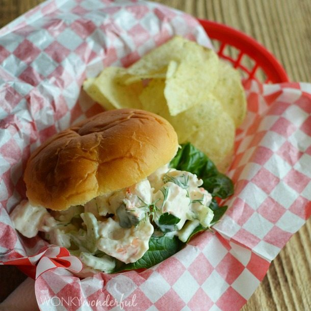 bread roll filled with shrimp salad in red basket with checkered paper