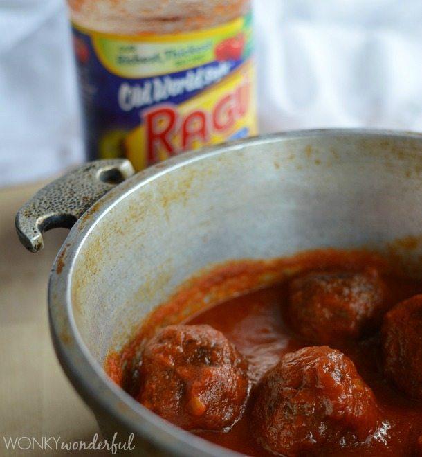 meatballs and sauce in metal pot next to jar of marinara sauce
