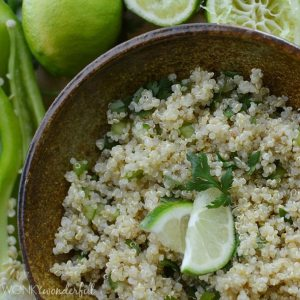 cooked quinoa topped with sliced limes and chopped cilantro in brown bowl