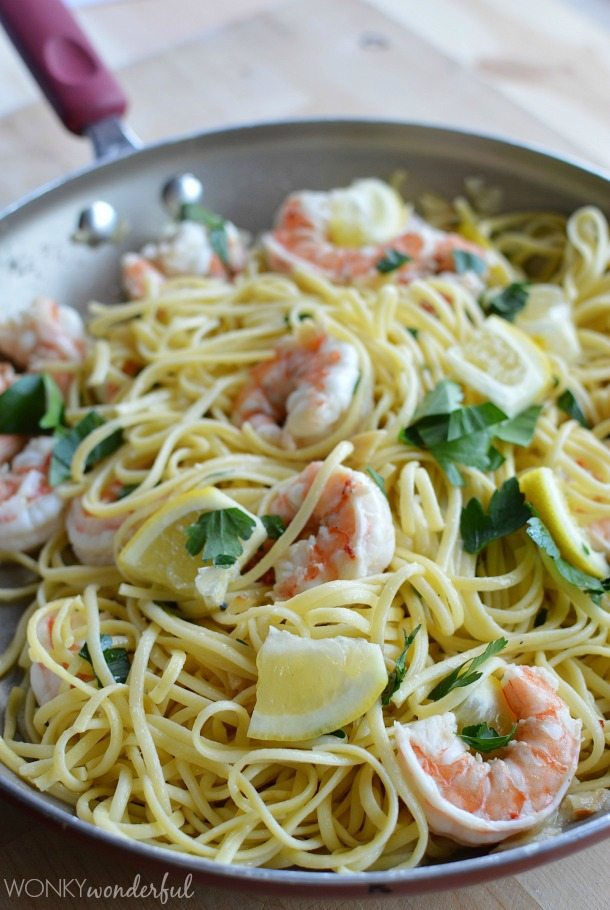 pasta and shrimp in red handled pan