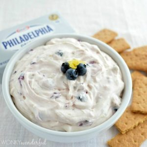 creamy dip topped with blueberries in white bowl next to graham crackers and cream cheese package