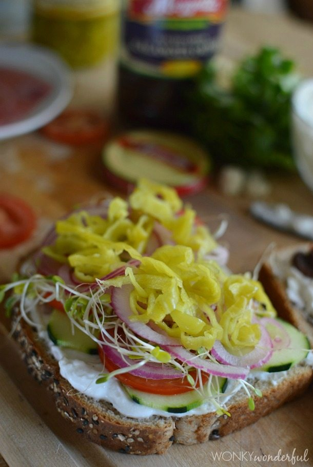 slice of bread topped with creamy spread and lots of veggies