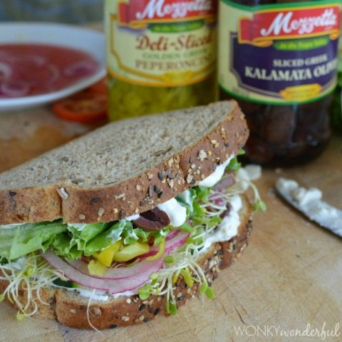 prepared sandwich on cutting board next to jars or pepperoncinis and olives