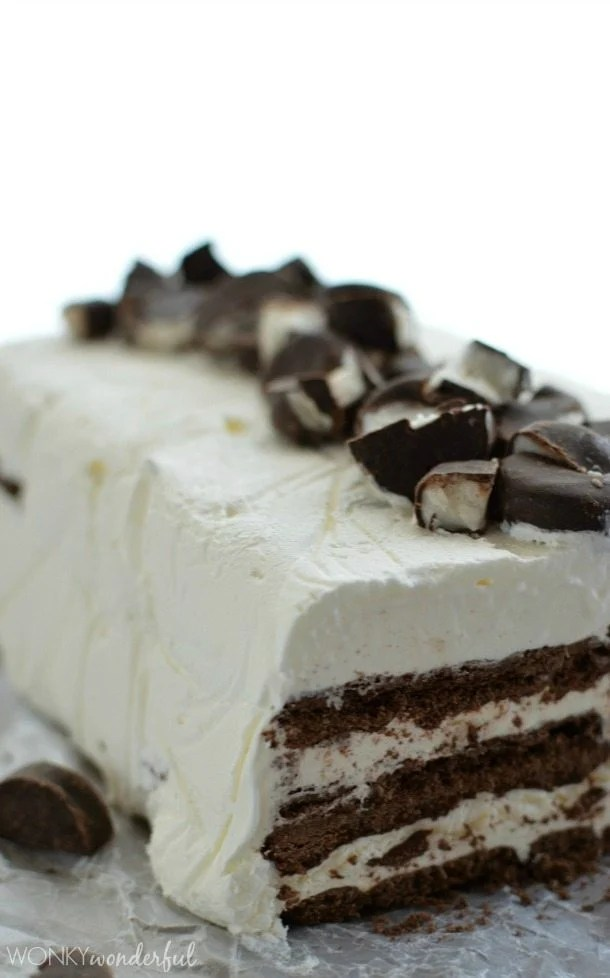 brown and white layered ice cream cake topped with brown and white chopped candy