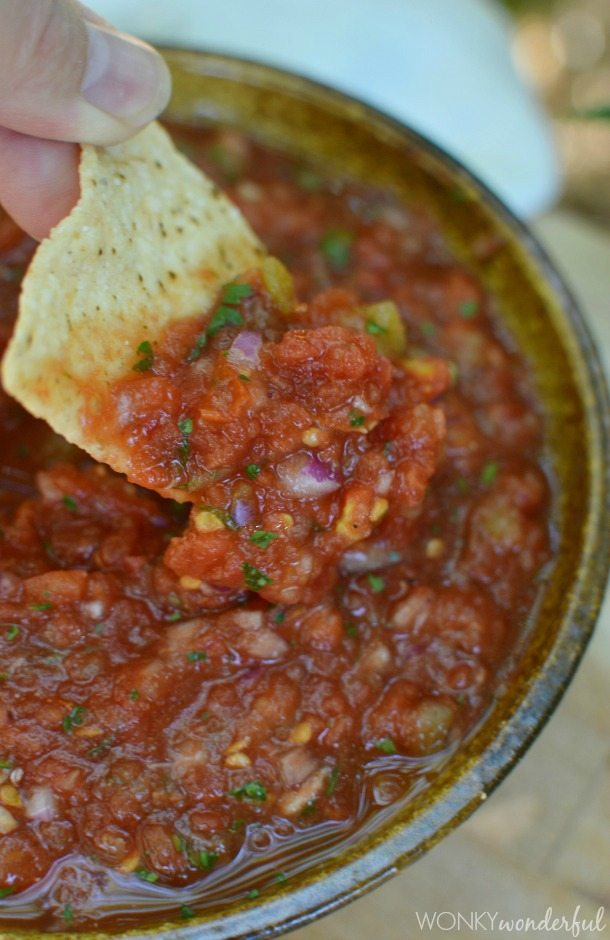 hand dipping tortilla chip into red salsa