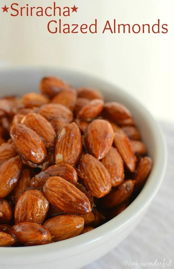 white bowl filled with reddish shiny almonds - photo text: sriracha glazed almonds
