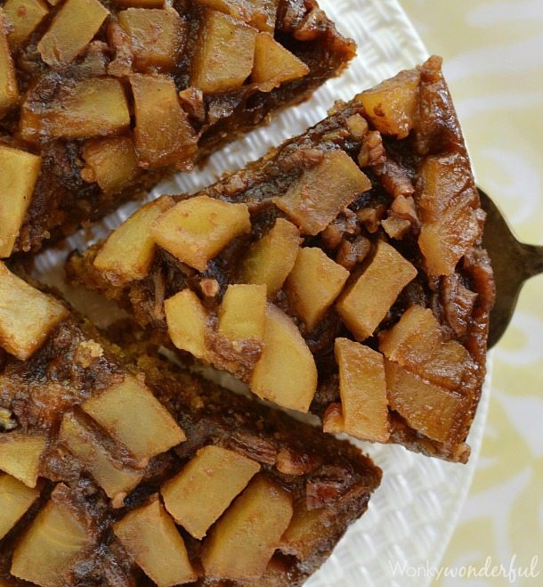 slices of cake topped with apple chunks, slice being removed