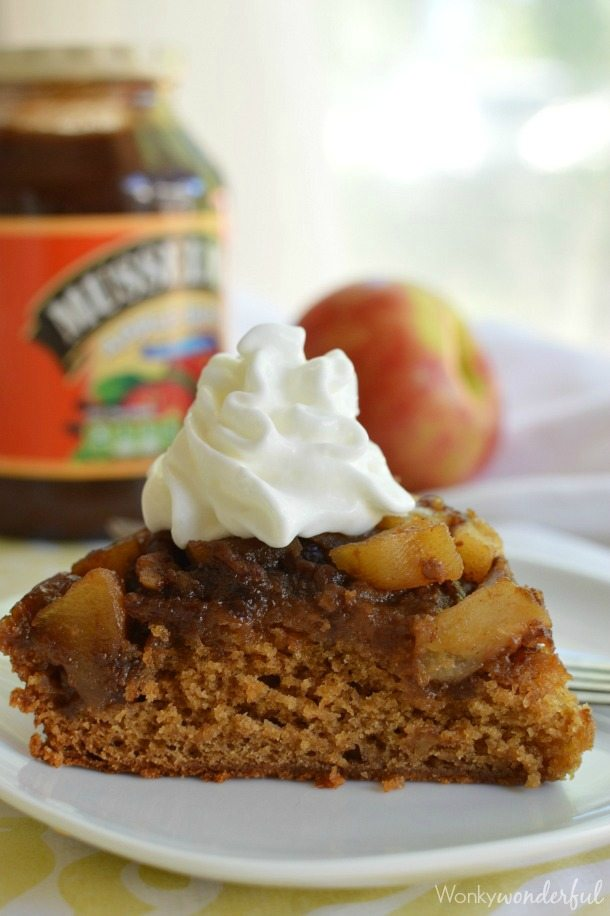 slice of brown cake with apple chunks topped with whipped cream