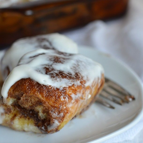 brown cinnamon roll topped with white glaze served on white plate with fork