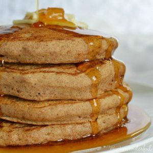 stack of four pancakes with butter and syrup