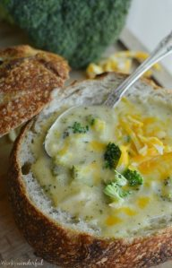 hollow bread bowl filled with soup and topped with broccoli and shredded cheese