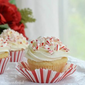 white cupcake with white frosting, red and white liner peeled off