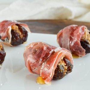 Prosciutto Wrapped Dated Stuffed with Goat Cheese and Fig Butter make the perfect hors d'oeuvres. Serve with a drizzle of honey and sprinkle of salt for the ultimate salty sweet appetizer recipe!