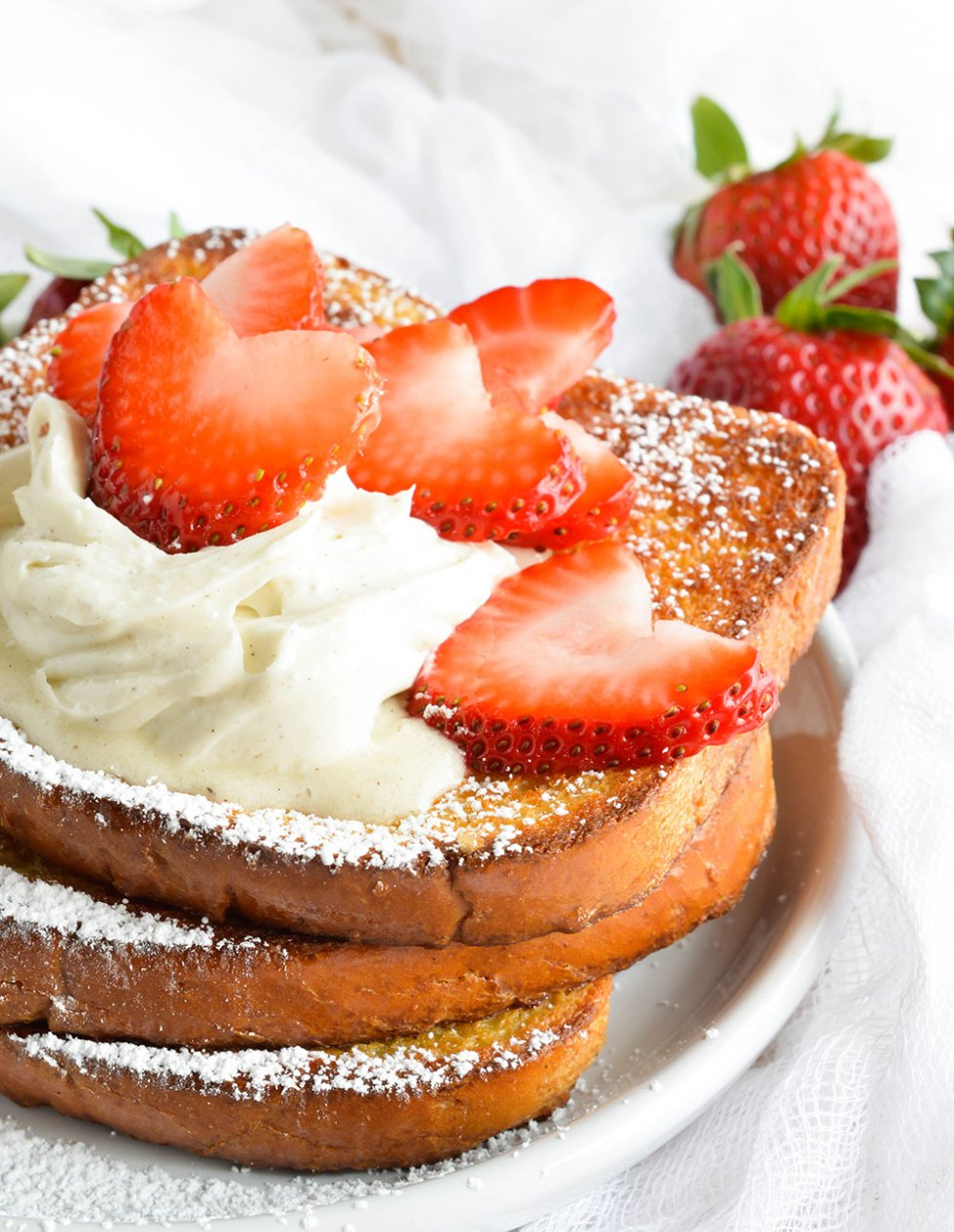 This Easy Baked French Toast Recipe is perfect for serving a crowd! Serve up this French Toast with Vanilla Mascarpone, Maple Syrup and Fresh Strawberries for the ultimate special occasion breakfast or brunch.