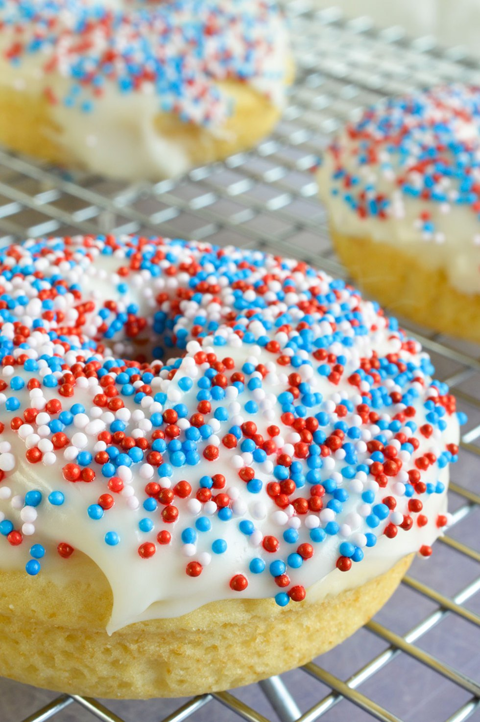 These Homemade Baked Donuts are a simple vanilla cake, thick glaze and nonpareils sprinkles. Red, White and Blue Doughnuts make the perfect 4th of July dessert recipe!