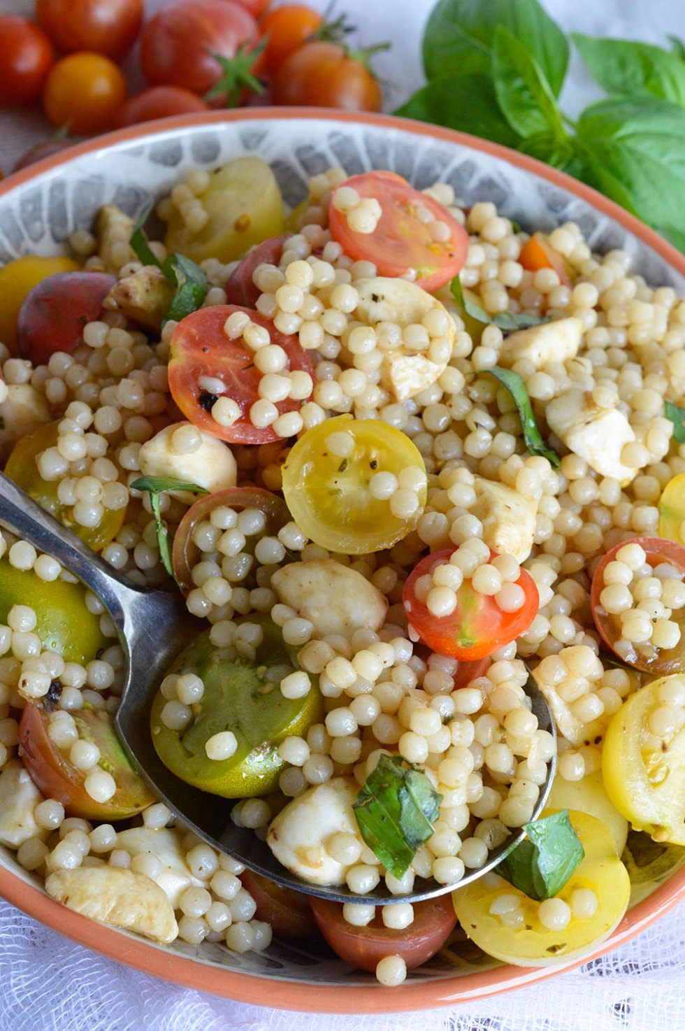 Caprese Couscous Salad Recipe - This fresh and easy side dish is full of flavor! Fresh tomato, mozzarella and basil with couscous and balsamic dressing. #epicurious #outofthekitchen