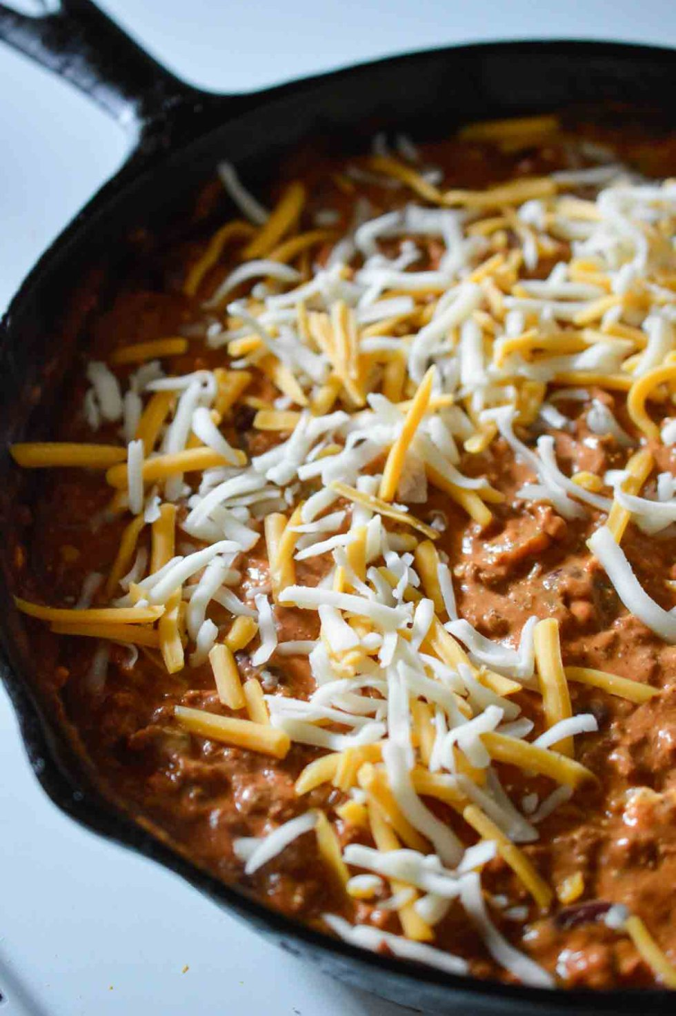 chili dip topped with shredded cheese in cast iron pan