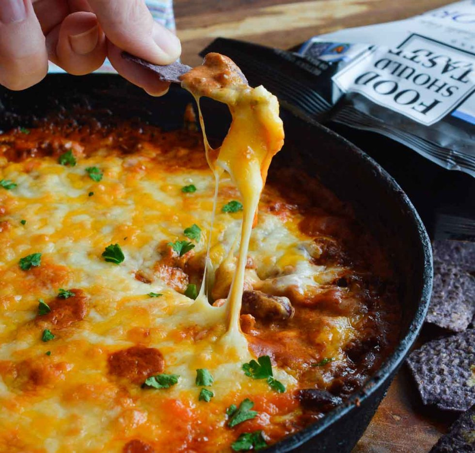 hand scooping chili cheese dip