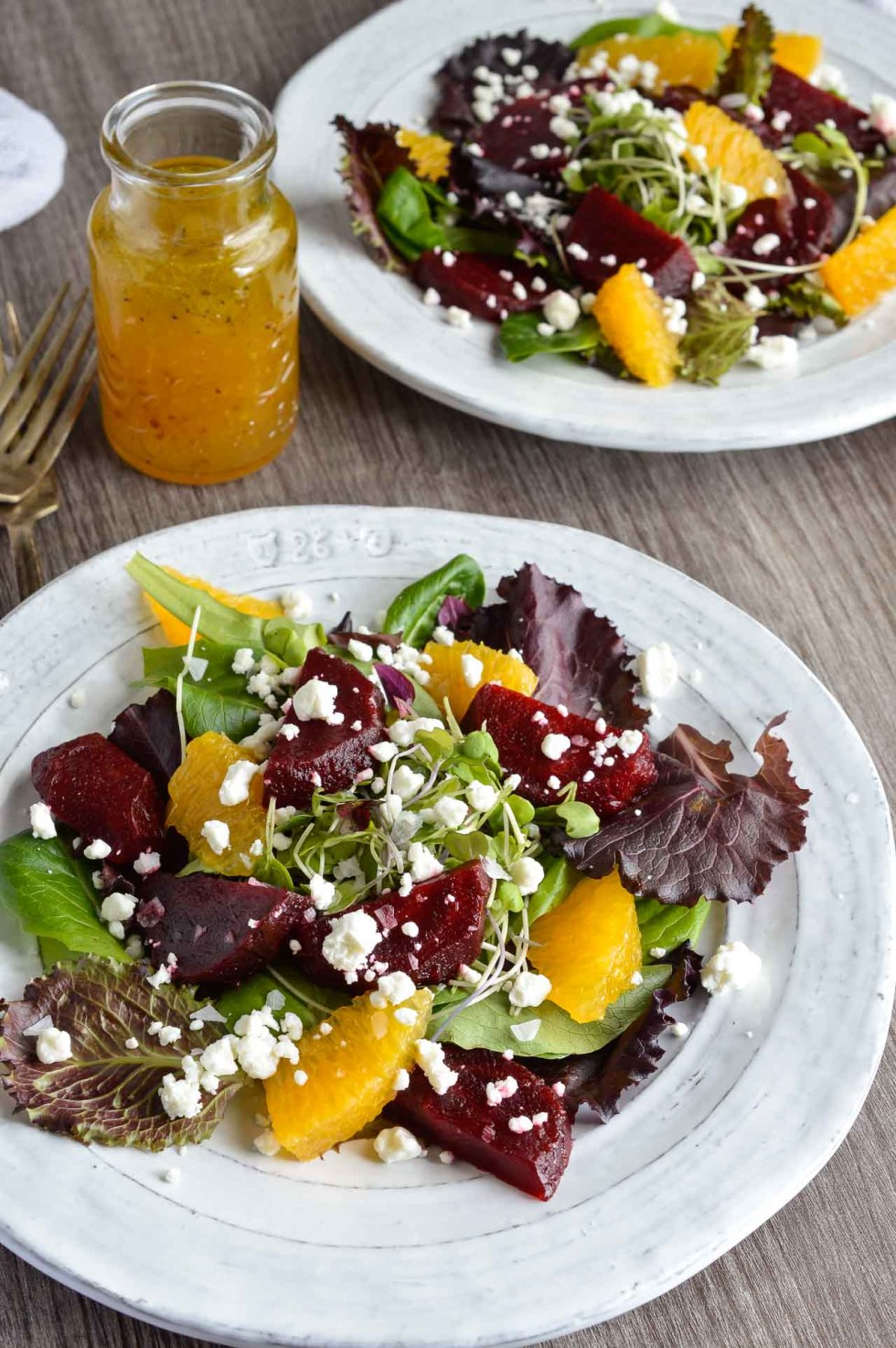 fresh beet salad with oranges, goat cheese and greens on a white plate