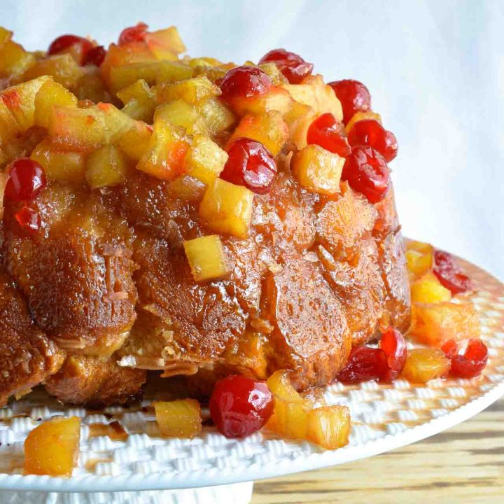 This Pineapple Upside Down Monkey Bread Recipe is just one of the fantastic dishes in the new Chew Cookbook! Pull-apart monkey bread topped with caramel, pineapple and cherries. The perfect dessert to share with a crowd!