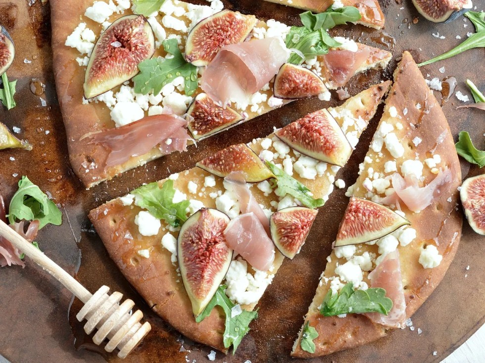 If you need a quick and easy dinner idea I am here for you! This Fig and Prosciutto Flatbread Pizza Recipe is great no-fuss meal. Fresh figs, crumbled goat cheese, prosciutto, peppery greens, honey and flaked salt make this flatbread pizza ultra delicious . . . and perfect with a glass of wine!