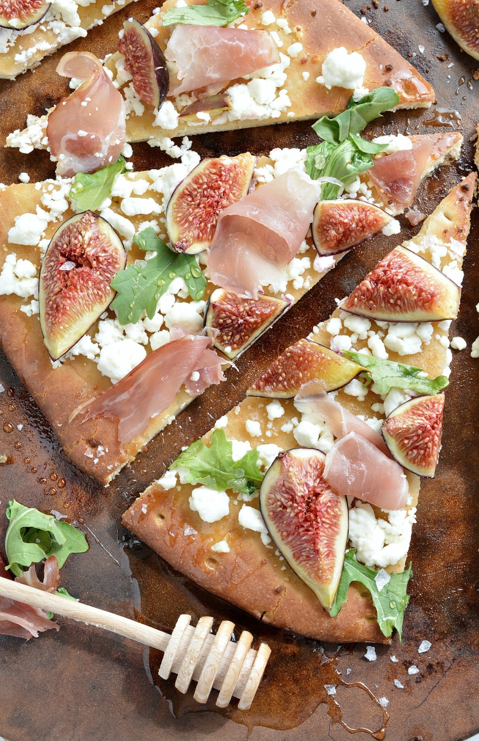 If you need a quick and easy dinner idea I am here for you! This Fig and Prosciutto Flatbread Pizza Recipe is a great no-fuss meal. Fresh figs, crumbled goat cheese, prosciutto, peppery greens, honey and flaked salt make this flatbread pizza ultra delicious . . . and perfect with a glass of wine! This meal comes together in about 15 minutes!