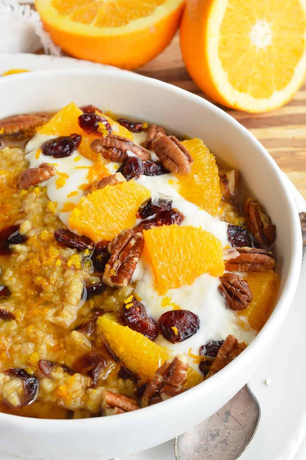 bowl filled with steel cut oatmeal, oranges, pecans and dried cranberries