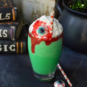 bright green milkshake topped with whipped cream, red sugar gel and gummy eyeball in clear glass