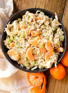 chicken salad With celery chunks and mandarin segments in black bowl