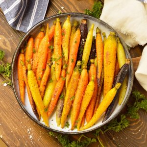 roasted rainbow carrots topped with parsley in blue and white serving dish