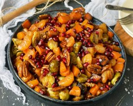 blue serving bowl filled with butternut squash chunks, orange segments, pecans and pomegranate seeds