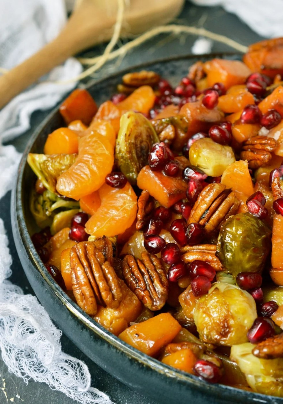Enjoy a healthy bowl full of Winter fruits and vegetables. This Butternut Squash Salad has roasted butternut squash, brussels sprouts, pecans, mandarin oranges and pomegranate seeds. Add the balsamic dressing and you have the ultimate nutritious, flavorful side dish! This is a Vegan, Paleo recipe with Whole30 options. #paleodiet #paleo #whole30recipes #vegan #veganrecipes