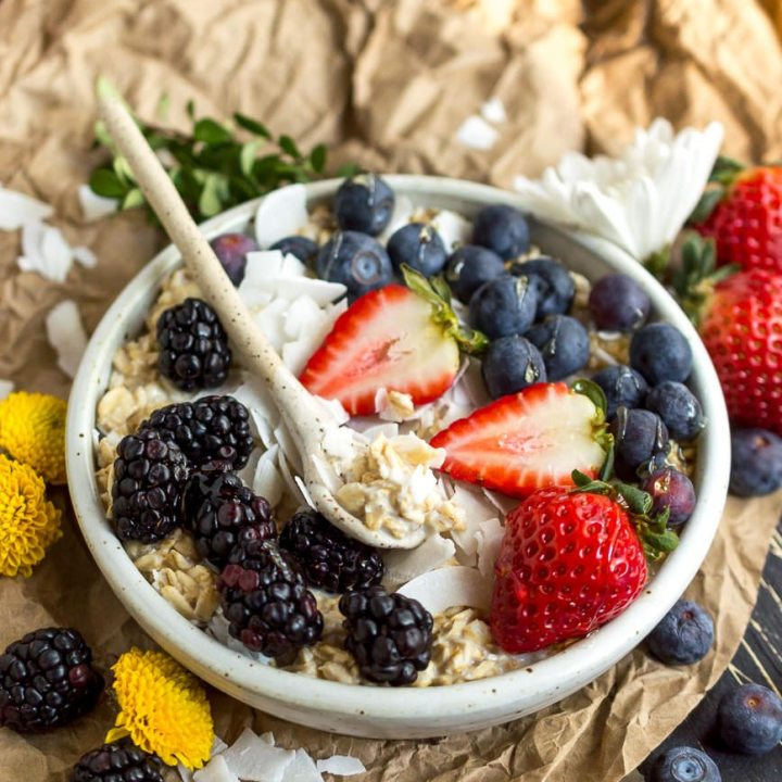 bright colorful berries over oatmeal in a white bowl with a white spoon
