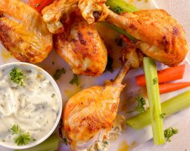 buffalo drumsticks, celery, carrots and blue cheese dip on white plate