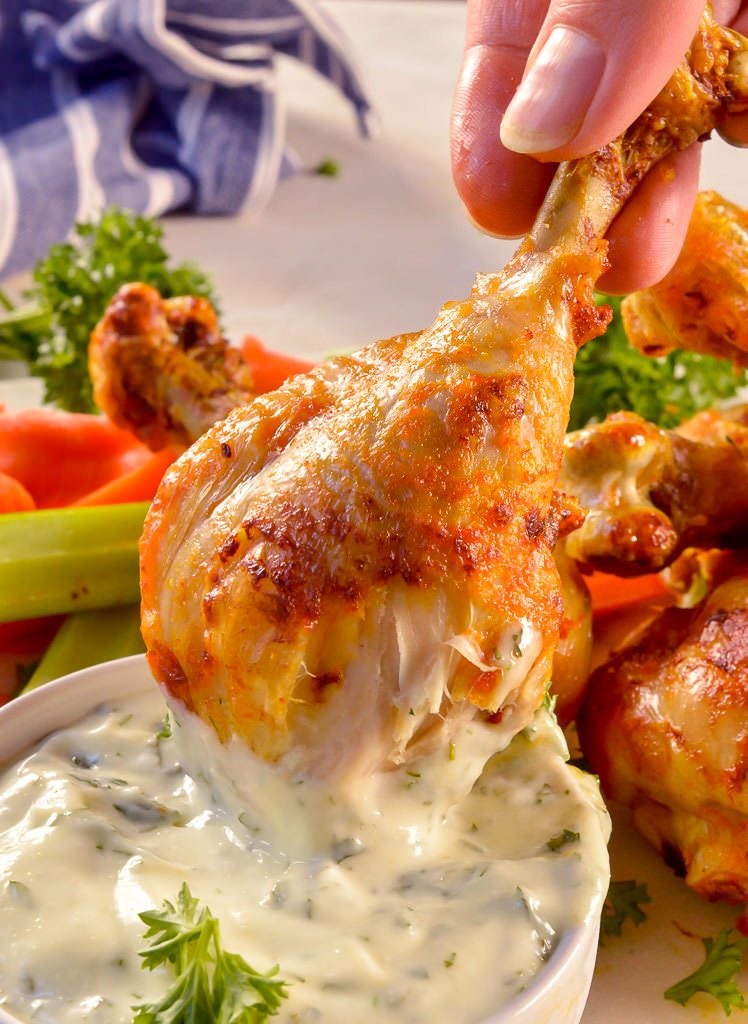 chicken drumstick coated with red buffalo sauce being dipped into ranch dip with carrots and celery in the background